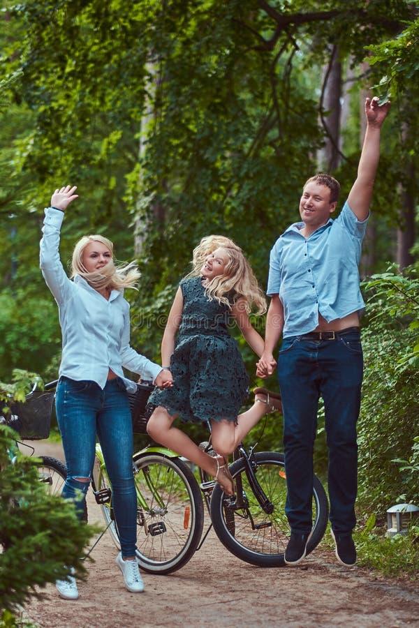 Atrakcyjna rodzina ubierał w przypadkowych ubraniach na rowerowej przejażdżce, w parku, zabawę i doskakiwanie obraz royalty free