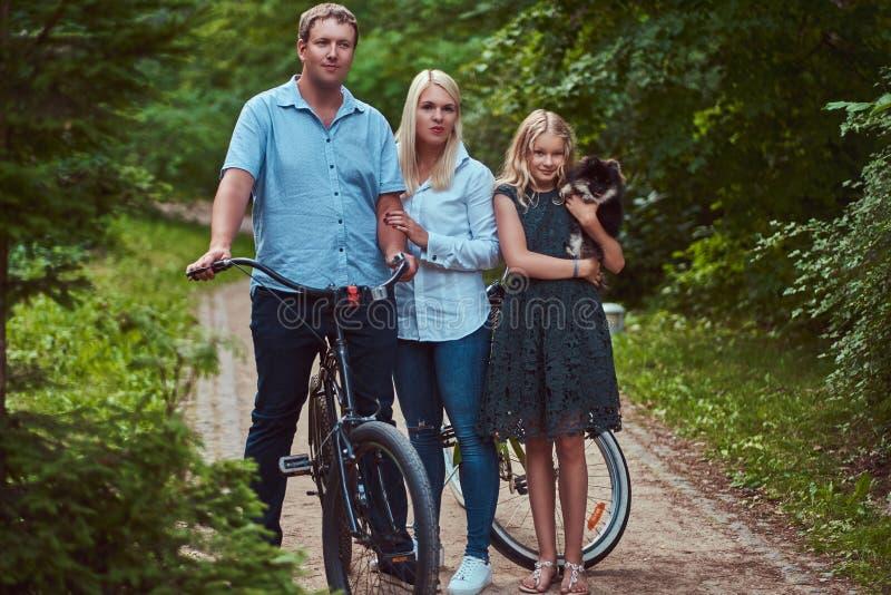 Atrakcyjna rodzina ubierał w przypadkowych ubraniach na rowerowej przejażdżce z ich ślicznym małym spitz psem, stoi w parku fotografia stock