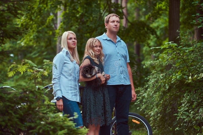 Atrakcyjna rodzina ubierał w przypadkowych ubraniach na rowerowej przejażdżce z ich ślicznym małym spitz psem, stoi w parku zdjęcie royalty free
