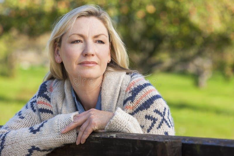 Atrakcyjna Rozważna W Średnim Wieku kobieta Odpoczywa na ogrodzeniu obraz royalty free