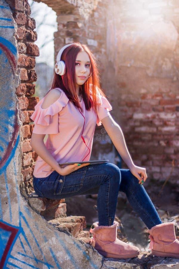 Atrakcyjna rudzielec dama słucha muzyka na hełmofonach na ruinach z cyfrową pastylką izoluje czerwone cegły retro dom w zmierzchu obraz royalty free