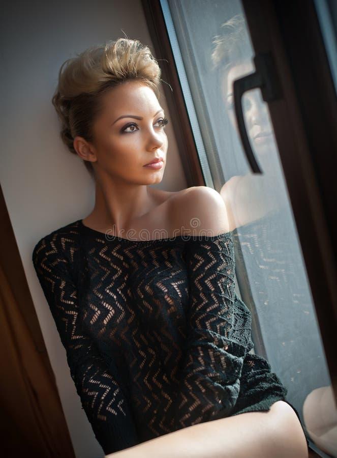 Atrakcyjna seksowna blondynka patrzeje na okno w świetle dziennym z czernią widzii bluzkę Portret zmysłowa krótka uczciwa włosian zdjęcie stock