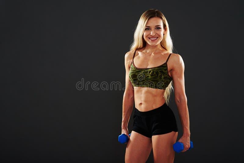 Atrakcyjna sportowa kobiety pozycja z dumbbells w jej rękach obraz royalty free