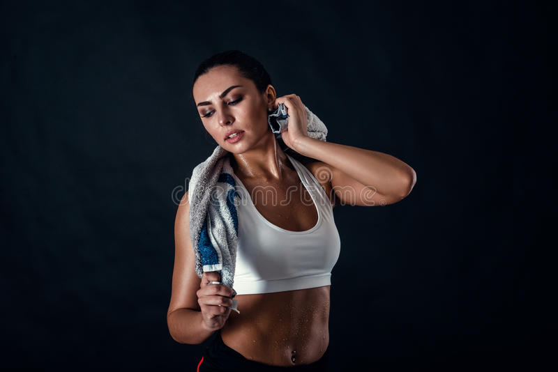 Atrakcyjna sportowa młoda kobieta z perfect ciałem jest ubranym sportswear pozuje z ręcznikiem przeciw czarnemu tłu fotografia stock