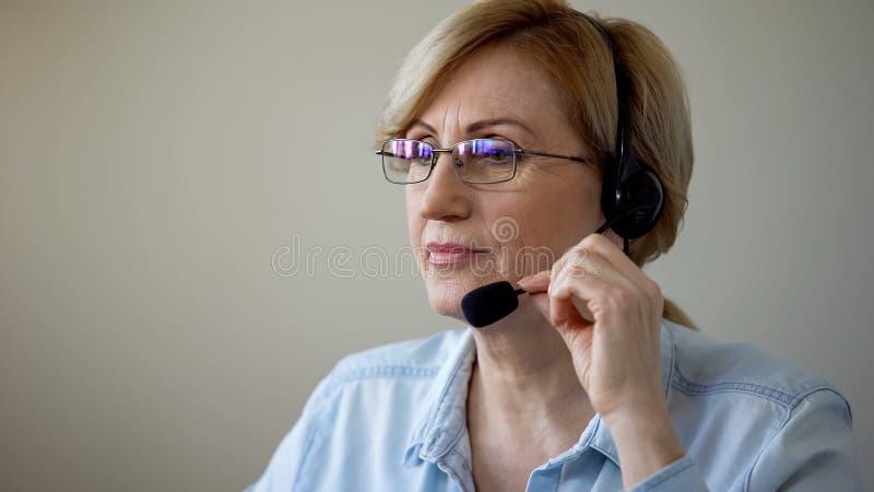 Atrakcyjna starsza dama z słuchawki agencji podróży ordynacyjnymi klientami, usługi obraz stock