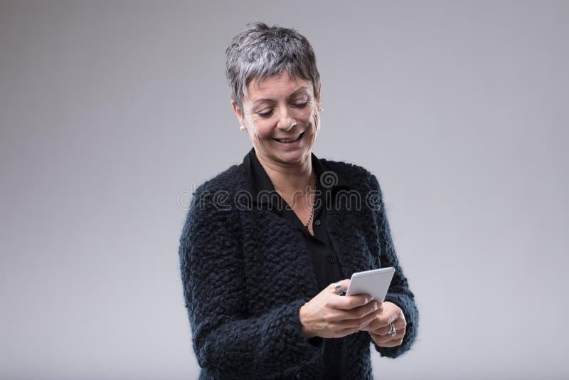 Atrakcyjna starsza kobieta pisać na maszynie na jej wiszącej ozdobie obrazy stock