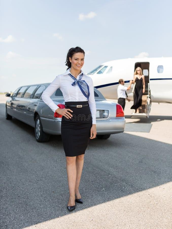 Atrakcyjna stewardesy pozycja Przeciw limuzynie obraz stock