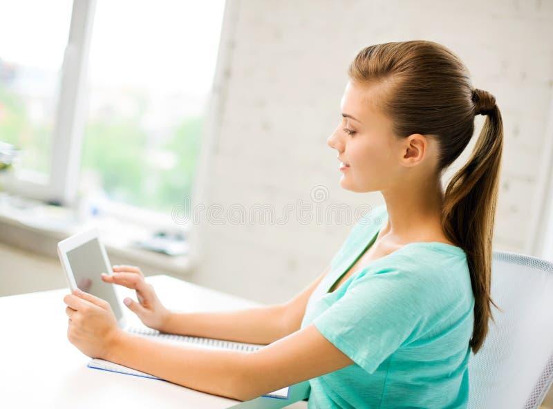 Atrakcyjna studencka dziewczyna używa pastylka komputer osobistego zdjęcia stock
