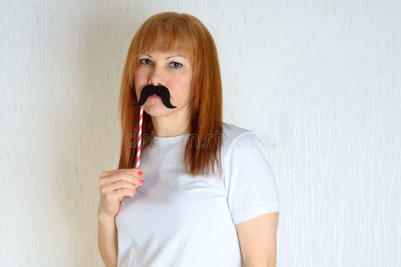Atrakcyjna szczęśliwa w średnim wieku kobieta ma zabawę z sfałszowanym wąsem na kiju zdjęcie royalty free