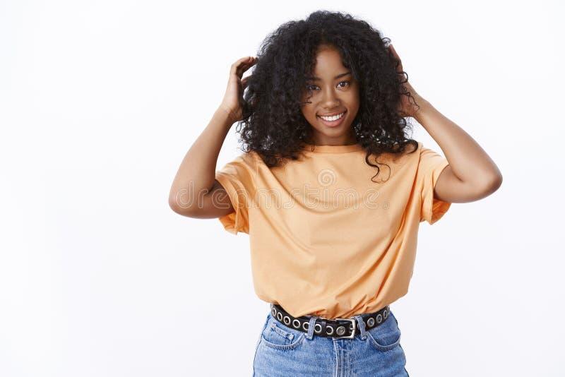 Atrakcyjna uśmiechnięta afroamerykańska młoda kobieta dotyka kędzierzawego pasemko czeka ostrzyżenie ono uśmiecha się szeroko sto zdjęcia royalty free