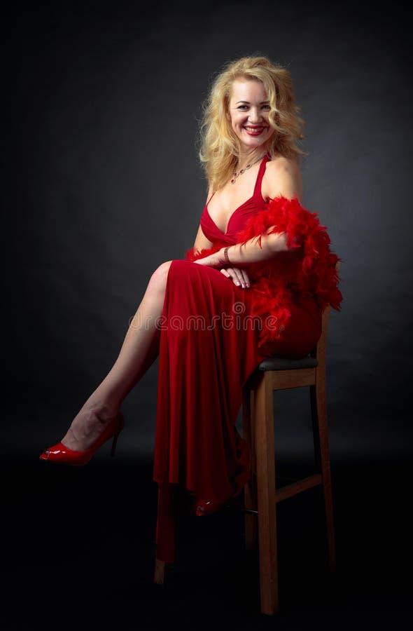 Atrakcyjna uśmiechnięta dojrzała kobieta w czerwonej wieczór sukni z puszystym piórkowym boa obraz royalty free