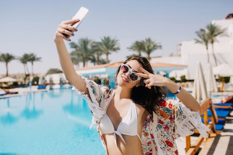 Atrakcyjna uśmiechnięta dziewczyna ma zabawę na kurorcie i robi selfie na południowym krajobrazie z egzotycznymi drzewkami palmow obrazy stock