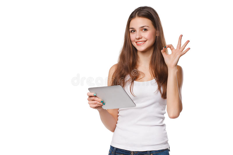 Atrakcyjna uśmiechnięta dziewczyna w białym koszulowym używa pastylka seansu ok znaku Kobieta z pastylka komputerem osobistym na  zdjęcia stock