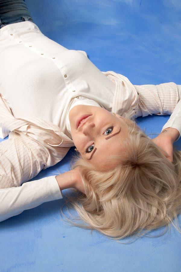 Atrakcyjna uśmiechnięta kobieta na błękitnym tle obrazy stock