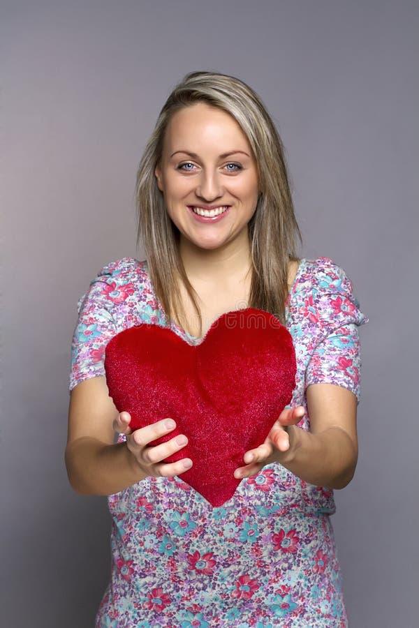 Atrakcyjna uśmiechnięta kobieta trzyma czerwonego serce obrazy stock