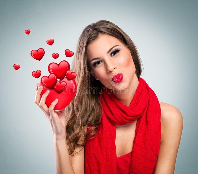 Atrakcyjna uśmiechnięta kobieta z czerwonym sercem zdjęcia royalty free