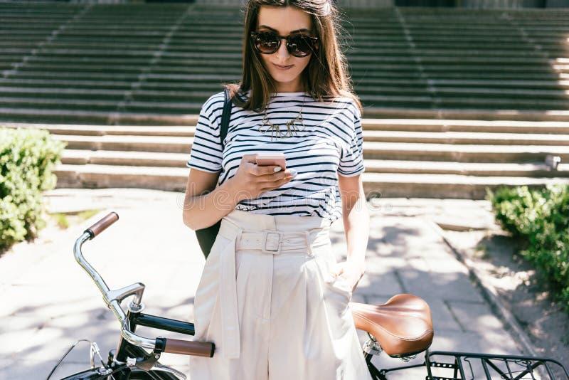 atrakcyjna uśmiechnięta młoda kobieta w okularach przeciwsłonecznych używać smartphone podczas gdy stojący z bicyklem fotografia royalty free