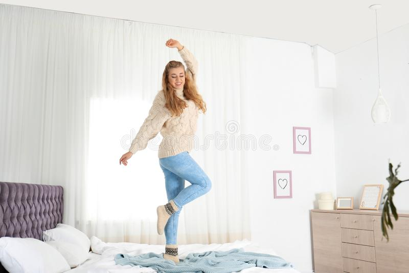 Atrakcyjna uśmiechnięta młoda kobieta w wygodnym ciepłym puloweru doskakiwaniu na łóżku zdjęcie stock