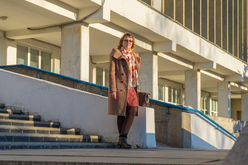 Atrakcyjna w średnim wieku kobieta jest ubranym elegancką żakiet pozycję z torbą na schodków krokach budynek biurowy w wczesnej w obrazy royalty free