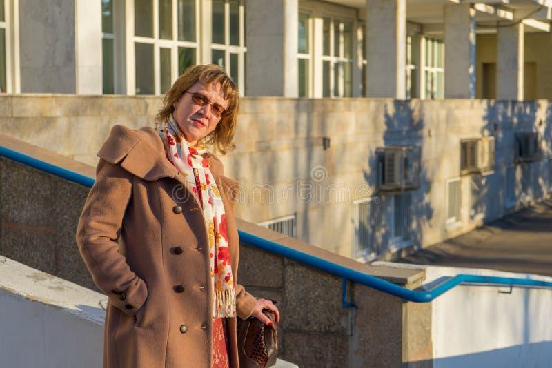 Atrakcyjna w średnim wieku kobieta jest ubranym elegancką żakiet pozycję z torbą na schodków krokach budynek biurowy w wczesnej w obraz royalty free