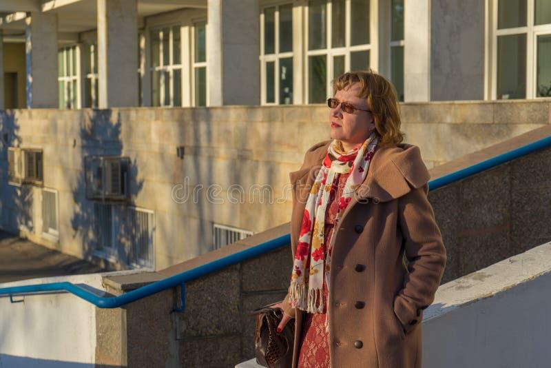 Atrakcyjna w średnim wieku kobieta jest ubranym elegancką żakiet pozycję z torbą na schodków krokach budynek biurowy w wczesnej w zdjęcie stock