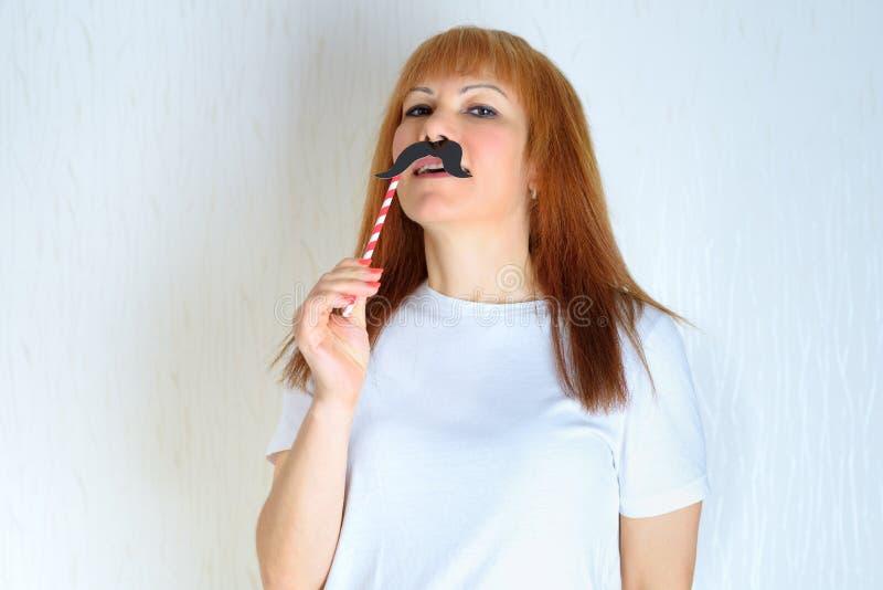 Atrakcyjna w średnim wieku kobieta ma zabawę z sfałszowanym wąsem zdjęcie royalty free