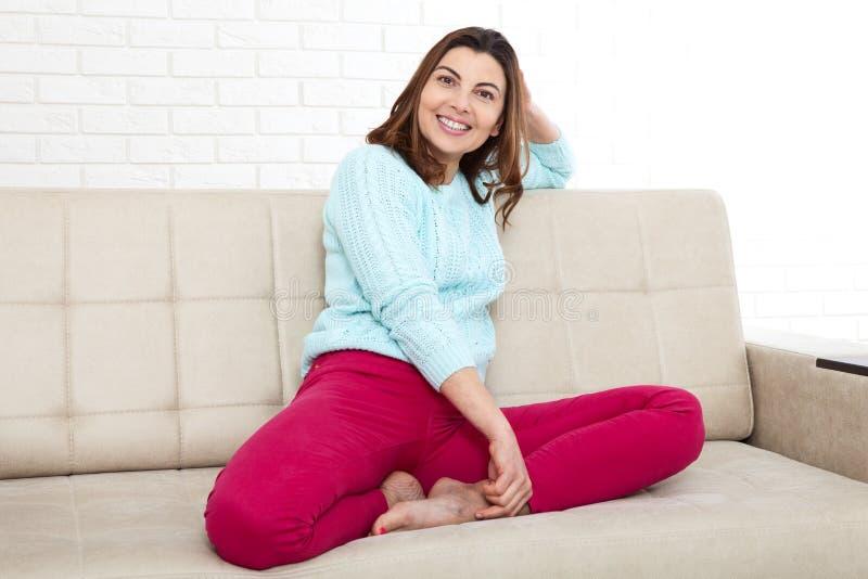 Atrakcyjna w średnim wieku kobieta patrzeje w kamerze relaksuje w domu E zdjęcie royalty free