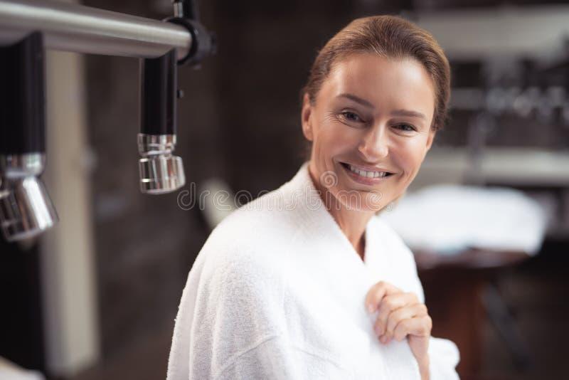 Atrakcyjna w średnim wieku kobieta pozuje przy zdroju salonem zdjęcia stock
