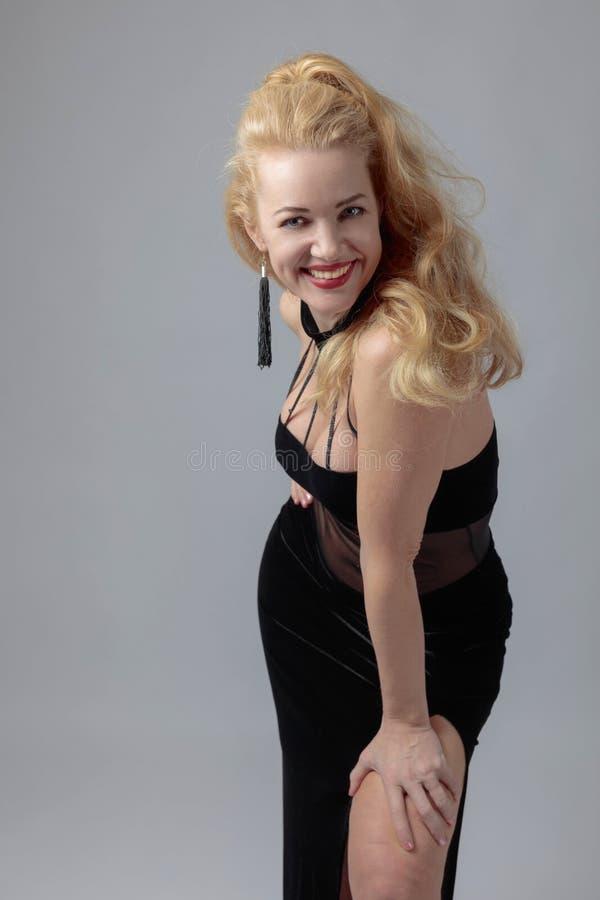 Atrakcyjna wiek średni kobieta w czarnej wieczór sukni zdjęcia royalty free