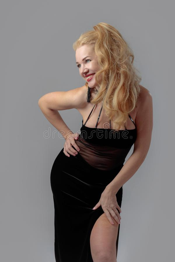 Atrakcyjna wiek średni kobieta w czarnej wieczór sukni obraz stock