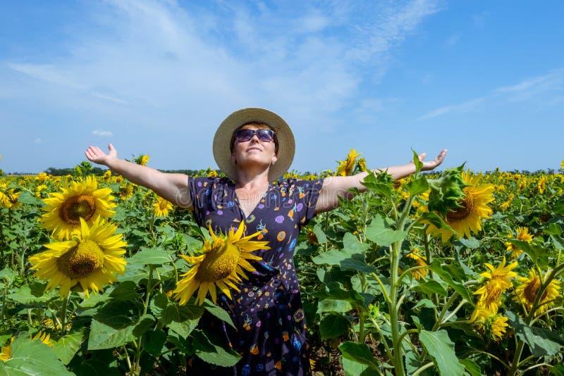 Atrakcyjna wiek średni kobieta w słomianym kapeluszu z rękami szeroko rozpościerać w słonecznika polu, świętuje wolność Pozytywny zdjęcie royalty free