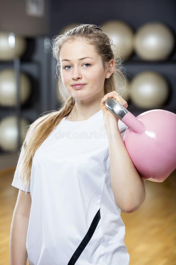 Atrakcyjna Zdecydowana kobieta Podnosi Kettlebell W Gym obrazy royalty free
