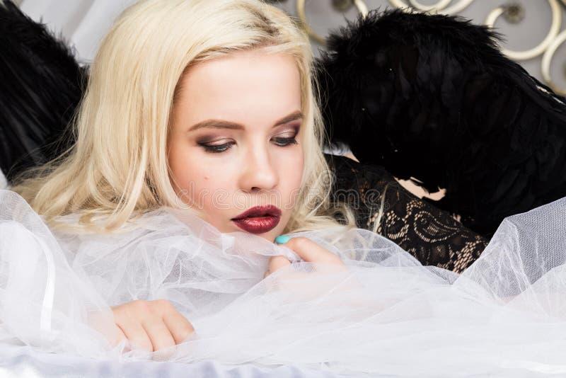 Atrakcyjna zmysłowa młoda seksowna kobieta jest ubranym czarnych bielizny i czerni skrzydła cieszy się na łóżku obrazy stock
