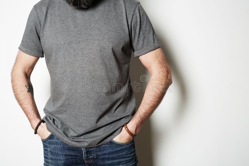 Atrakcyjne brutalne tatuować brodate facet pozy w niebieskich dżinsach i puste miejsce koszulki premii lata szarej bawełnie na obrazy royalty free