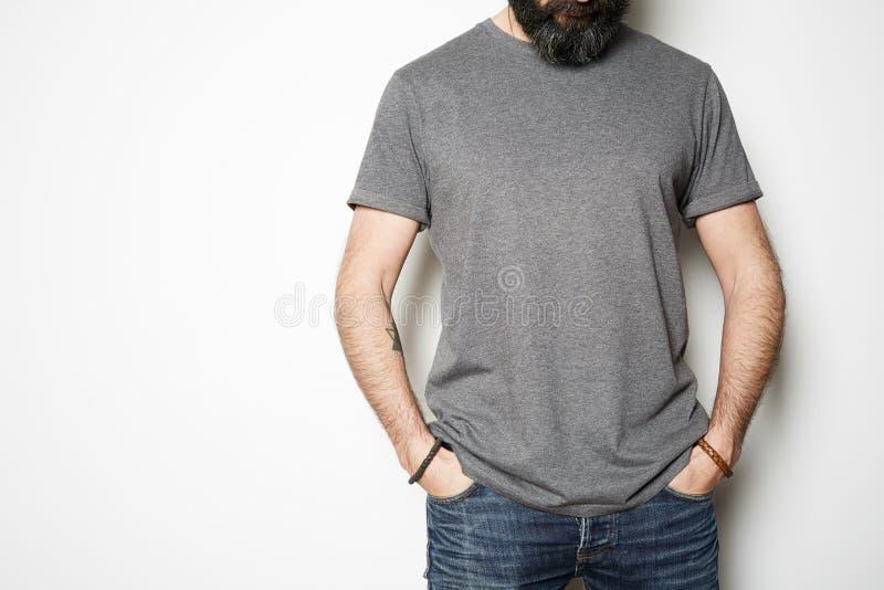 Atrakcyjne brutalne tatuować brodate facet pozy w niebieskich dżinsach i puste miejsce koszulki premii lata szarej bawełnie na zdjęcie royalty free