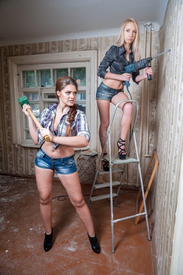 Atrakcyjne kobiety naprawiają w mieszkaniu obrazy stock