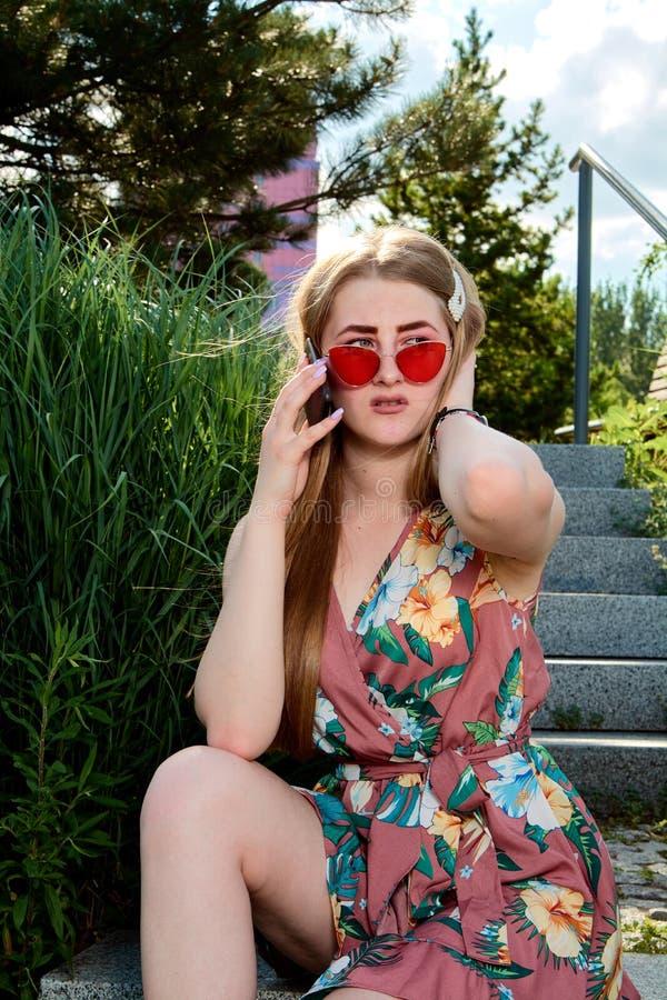 atrakcyjne kobiety young Czerwoni okulary przeciwsłoneczni, kolor suknia, telefon komórkowy, 5G, 4G, 3G, 2G, LTE sieć obraz stock