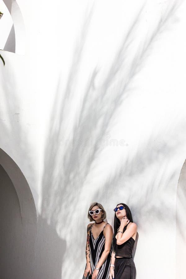 atrakcyjne modne dziewczyny w okularach przeciwsłonecznych pozuje blisko białego budynku przy kurortem obraz stock