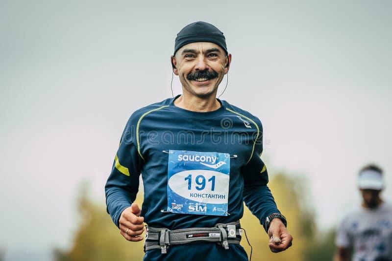 Atrakcyjnego atleta biegacza w średnim wieku dystansowy bieg i ono uśmiecha się obraz stock