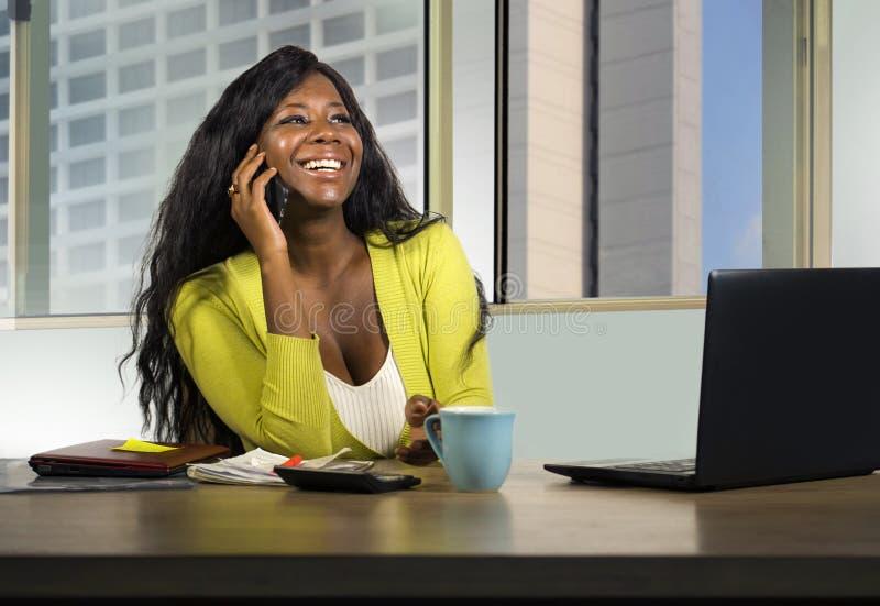 Atrakcyjnego czarnego afrykanina bizneswomanu Amerykański pracować ufny przy komputerowym biurkiem opowiada na telefonie komórkow obrazy stock