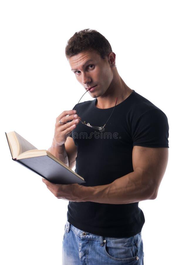 Atrakcyjnego i sportowego młodego człowieka czytelnicza książka zdjęcia royalty free