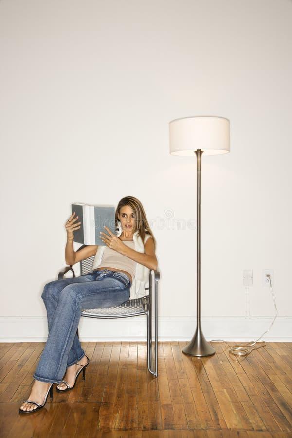 atrakcyjnego krzesła czytelniczy kobiety potomstwa obraz royalty free