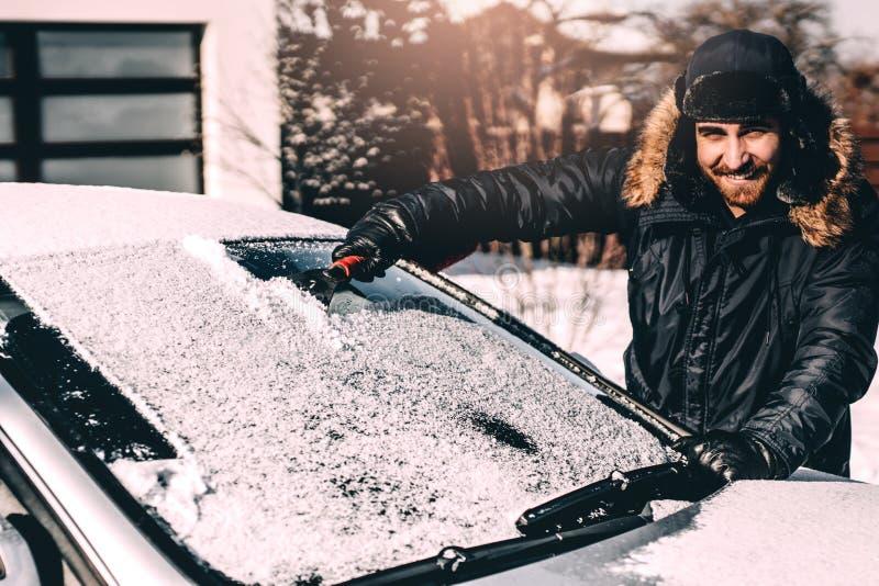 Atrakcyjnego mężczyzny ono uśmiecha się i czyści śnieg z jego samochodu, pracujący podczas zimy i jechać obraz stock