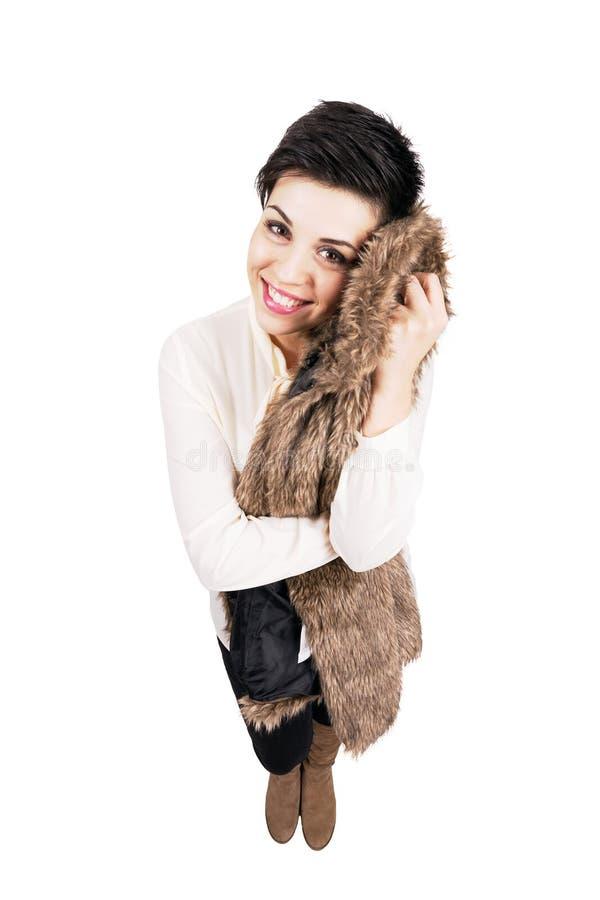 Atrakcyjnego młodego eleganckiego kobiety mienia miękki futerkowy żakiet przeciw jej policzkowi obrazy stock