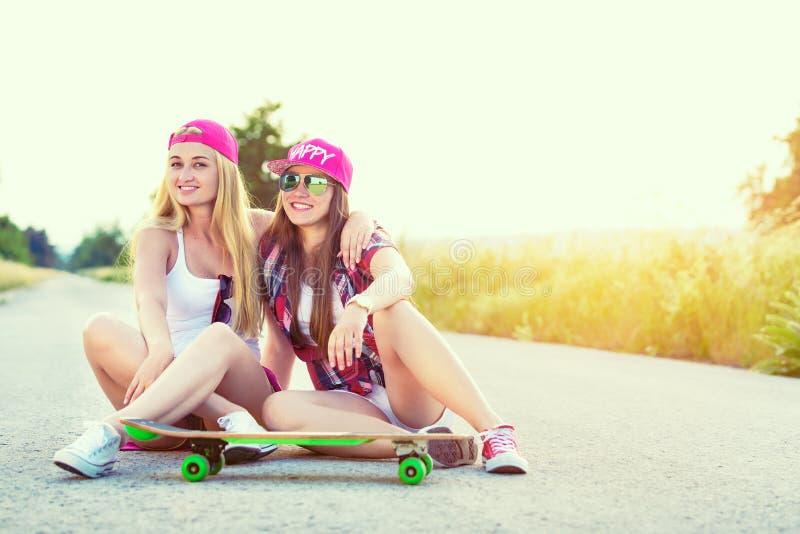 Atrakcyjnego uśmiechniętego modnisia nastoletni przyjaciele z deskorolka zdjęcie stock