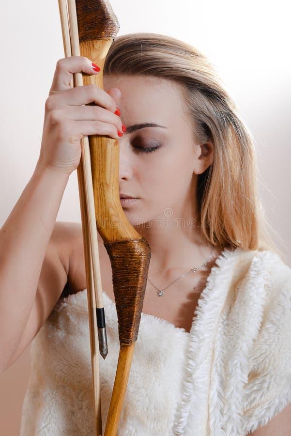 Atrakcyjnej czułej szczerej blond młodej kobiety dziewczyny mienia łęku i strzała piękni oczy zamykali być ubranym kaross lub bia obraz stock