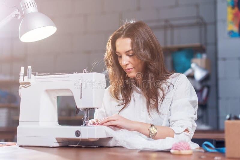 Atrakcyjnej Kaukaskiej szwaczki pracujący zaszywanie z szwalną maszyną przy jej miejscem pracy w pracownianym loft wnętrzu zdjęcia royalty free