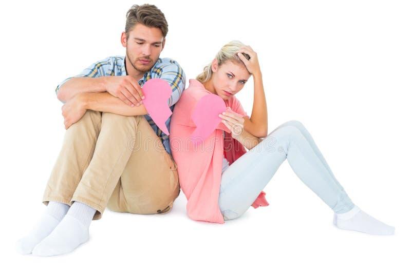 Atrakcyjnej potomstwo pary siedzący mienie dwa połówki złamane serce obrazy stock