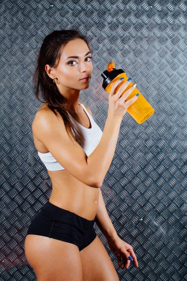Atrakcyjnej sprawności fizycznej kobiety salowy portret z butelką zdjęcia stock