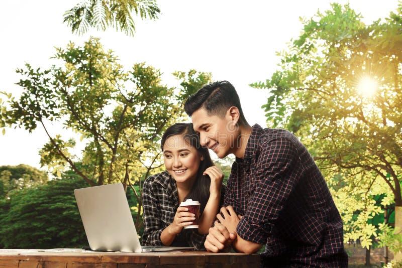 Atrakcyjni azjatykci pary dopatrywania środki na laptopie zdjęcie stock